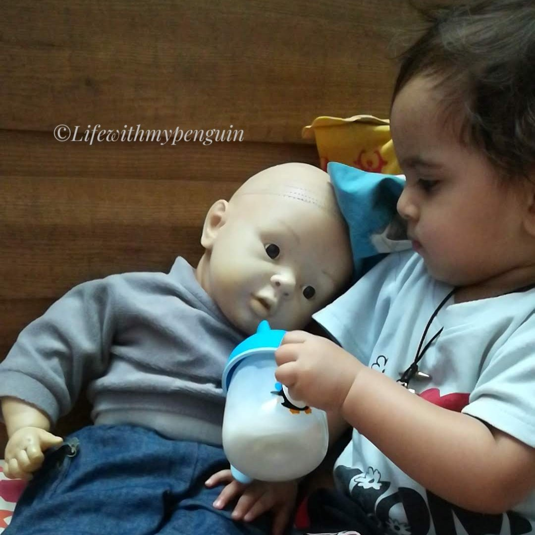 toddler boy playing with doll